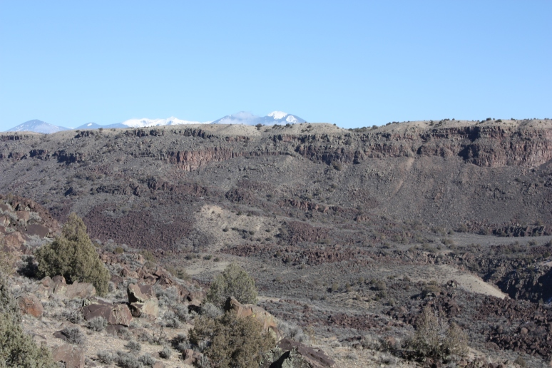 The Rocky Mountains behind Taos are just visible above the gorge rim.